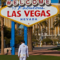 A man dressed as Elvis Presley walks below the welcome sign on the Las Vegas Strip. The sign dates back to the early development era of Las Vegas and has been refurbished, complete with a park for tourism photos.