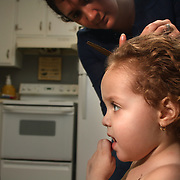 On December 27, 2012 two year old Holly Larue Frizzelle was diagnosed with Acute Lymphoblastic Leukemia. What began as a stomach ache and visit to her regular pediatrician led to a hospital admission, transport to the University of North Carolina Children's Hospital, and more than two years of treatment. Leilani Frizzelle cuts her daughter Holly Larue Frizzelle's hair at their home. Larue's hair had begun to thin during chemotherapy and Leilani cut to blend in until it fell out.