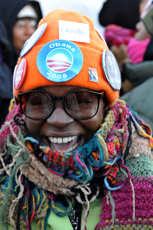Her hat covered with campagin pins, a woman laughs with friends while in line to attend President-elect Obama's pre-inauguration rally in Wilmington, Delaware, one in a crowd of thousands that braved sub-zero temperatures to lend support.  The President and Vice President elect traveled by train on a Whistle Stop Tour, opening Inauguration celebrations with rallies in Philadelphia, Wilmington, and Baltimore before their final arrival in Washington, D.C.  The inauguration takes place on January 20, 2009, swearing Obama in as the 44th President of the United States of America.¬?