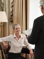 Middle-aged business man standing in front of business woman sitting down at desk