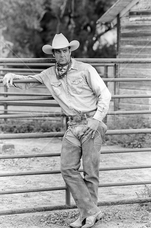 handsome cowboy outdoors leaning on a fence at a ranch
