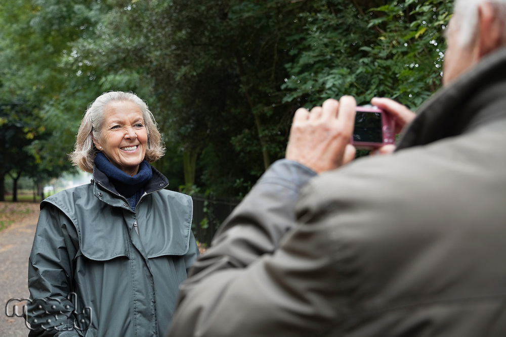 Happy senior woman being photographed by husband at park
