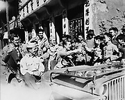 Joe E Brown (1892-1973) American actor and comedian driving jeep loaded with American GIs seeing the sights in China.   Brown giving thumbs up sign to Chinese children, 1942 or 1943.
