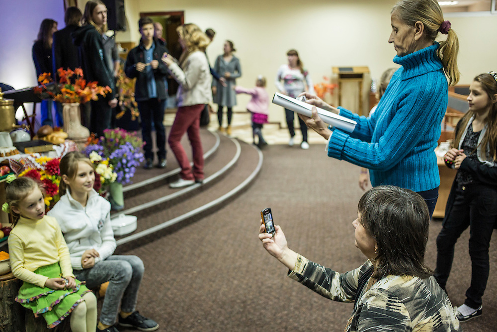 DNIPROPETROVSK, UKRAINE - OCTOBER 12: Natasha (lower R) and Svitlana Kostromina (upper R), who both fled with their families from Luhansk due to fighting, photograph their granddaughters after a service at the Good News Evangelical Church on October 12, 2014 in Dnipropetrovsk, Ukraine. Kostromina, her daughter, and her granddaughter are living with a family that is part of the congregation. The United Nations has registered more than 360,000 people who have been forced to leave their homes due to fighting in the East, though the true number is believed to be much higher.(Photo by Brendan Hoffman/Getty Images) *** Local Caption *** Svitlana Kostromina