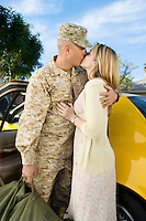 Soldier kissing wife by car