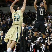 Central Florida guard Isaac Sosa (11) shoots against Shaun Noriega (22) during the NCAA basketball game against the USF Bulls at the UCF Arena on November 18, 2010 in Orlando, Florida. UCF won the game 65-59. (AP Photo/Alex Menendez)