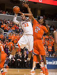 Virginia forward Mike Scott (32) puts a shot up past Clemson forward/center Raymond Sykes (12).  The Virginia Cavaliers defeated the #12 ranked Clemson Tigers in overtime 85-81 at the John Paul Jones Arena on the Grounds of the University of Virginia in Charlottesville, VA on February 15, 2009.