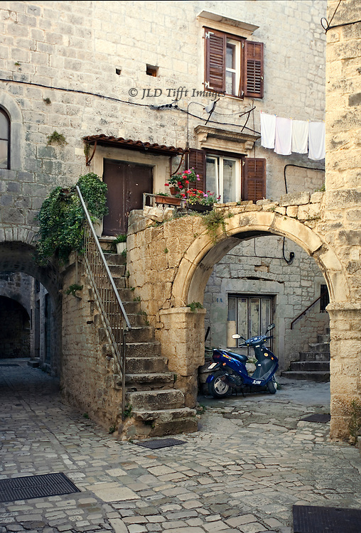 Trogir: small courtyard with arch, stairway, laundry hanging out to dry, and a motorbike.  Roman and medieval structures still in use as people clearly still live in them. Electric wires strung along the outside walls.