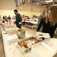 """Elizabeth Coleman, right, begins making a """"to-go"""" box at Thursday's annual Thanksgiving dinner atthe Salvation Army on Carnation Street in Tupelo."""