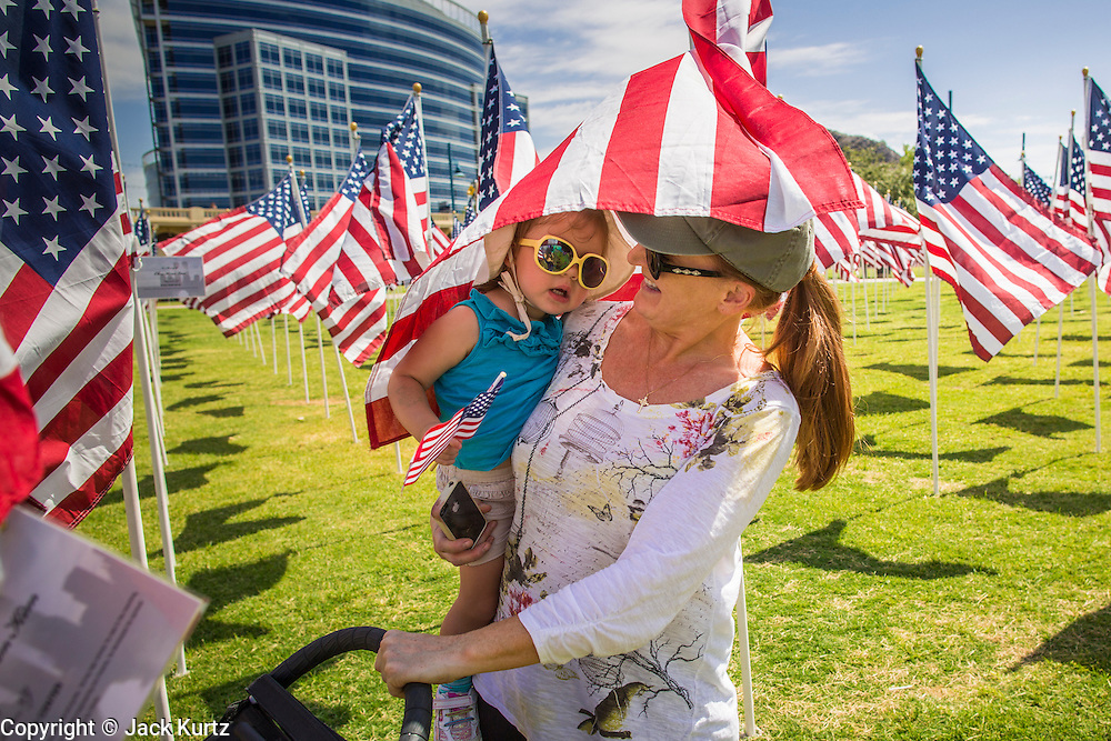 10 SEPTEMBER 2012 - TEMPE, AZ:      JODY TIERNEY and her granddaughter, MIKAYLEE, 19 months old, walk through the Healing Field in Tempe, AZ, Monday. The Exchange Club of Tempe and the city of Tempe are hosting the 9th Annual Healing Field display. The annual event posts three thousand American flags in the Tempe Beach Park. The flags are 3?X5?  and stand 8? tall. The display is a tribute to those who died in the terrorist attacks of September 11, 2001. Nearly 3,000 people were killed when terrorists affiliated Al-Qaeda crashed commercial airliners into the World Trade Center in New York, the Pentagon in Arlington, VA, and a field in Ohio.   PHOTO BY JACK KURTZ