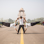 NEW DELHI, INDIA - NOVEMBER, 08, 2016: Members of the Alphapack group demonstrate a move known as the human flag at India gate in New Delhi, India.  L-R: Kritarth Chauhan, 19, Harshit Sharma, 19, Kunal Mahour, 20.<br />