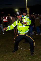 © Licensed to London News Pictures. 20/06/2015. Salisbury, UK. A police officer entertaining visitors at the summer solstice dawn celebrations as druids, pagans and revellers gathered the night before the Summer Solstice sunrise at Stonehenge on June 20, 2015 in Wiltshire, England. Thousands of revellers gather at the 5,000 year old stone circle in Wiltshire to see the sunrise on the Summer Solstice dawn. The solstice sunrise marks the longest day of the year in the Northern Hemisphere. Photo credit: Tolga Akmen/LNP