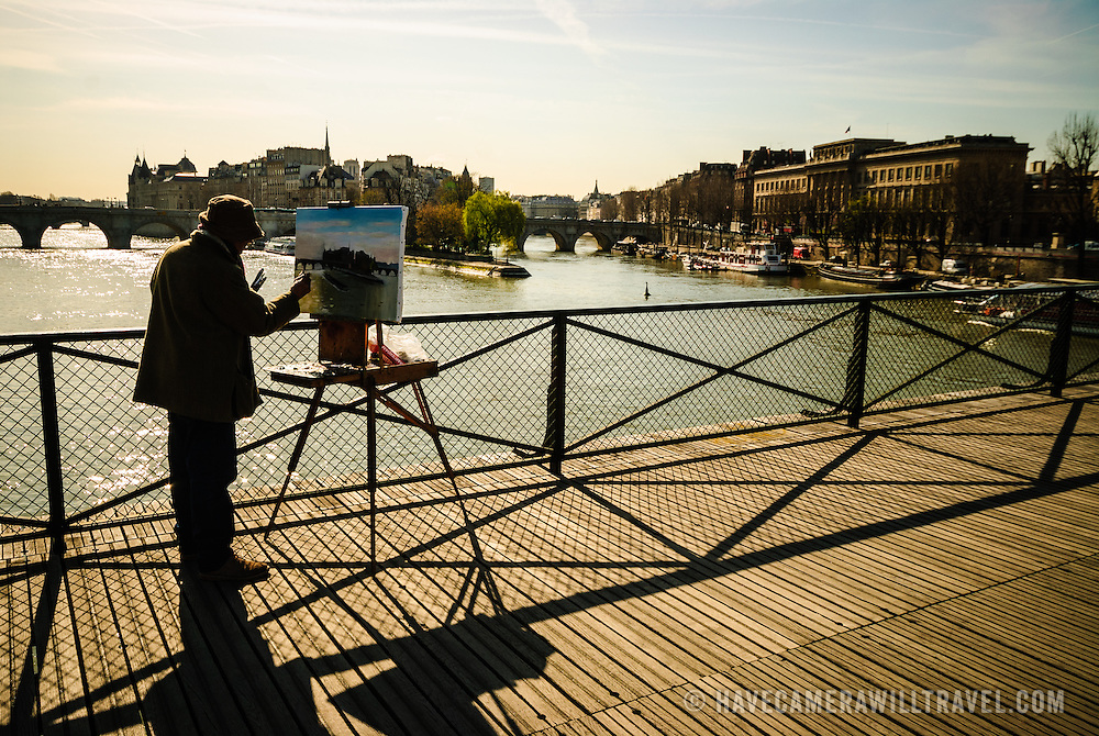 Man painting view of Seine and Paris skyline from bridge. Backlighting