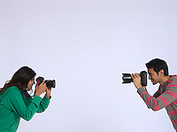 Young woman and young man photographing each other studio shot