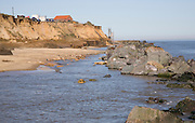Cliff top buildings at risk of coastal erosion, Happisburgh, Norfolk, England rock armour boulders used as defence