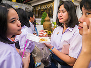"27 NOVEMBER 2012 - BANGKOK, THAILAND:  School girls share a snack on the midway at the Wat Saket Temple Fair in Bangkok. Thailand is facing a rising tide of gun violence and is wrestling with how to curb it. Despite strict gun control laws, more and more guns are showing up in the country. Wat Saket, popularly known as the Golden Mount or ""Phu Khao Thong,"" is one of the most popular and oldest Buddhist temples in Bangkok. It dates to the Ayutthaya period (roughly 1350-1767 AD) and was renovated extensively when the Siamese fled Ayutthaya and established their new capitol in Bangkok. The temple holds an annual fair in November, the week of the full moon. It's one of the most popular temple fairs in Bangkok. The fair draws people from across Bangkok and spills out in the streets around the temple.   PHOTO BY JACK KURTZ"
