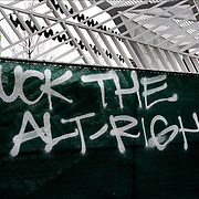 Spray paint white graffiti &quot;Fuck The Alt-Right&quot; on dark fence.<br />