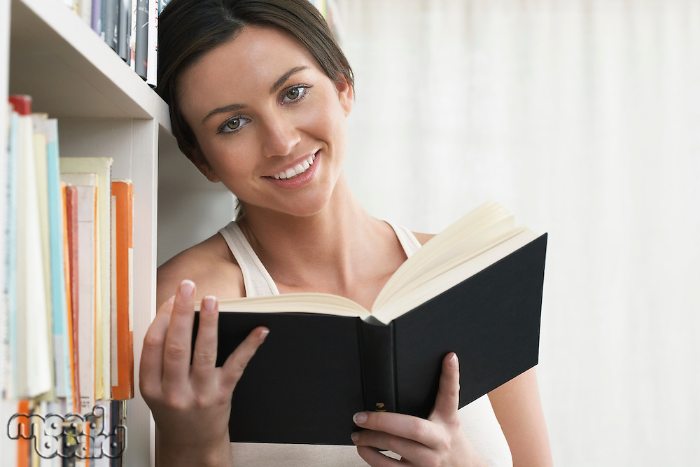 Young woman holding book leaning against bookshelf portrait