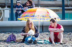 © London news pictures. 25/03/2017. Aberystwyth, UK.<br /> A young couple with a pet white rabbit  on the beach on an afternoon of glorious sunshine and clear blue skies in Aberystwyth on the west wales coast, with temperatures expected to reach 18 or 19ºc by the afternoon. Sheltered from the cooling effects of an easterly wind, West Wales is expected to be the warmest pace in the UK today (Sat). Photo credit: Keith Morris/LNP