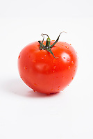 Close-up of fresh red tomato with water droplets over white background
