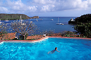Person swimming in pool, Hotel Secret Harbour, view over Mt. Hartman Bay with sailboats, Grenada, Caribbean