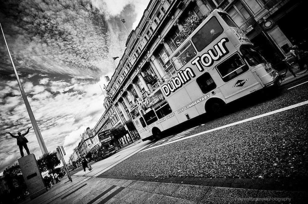 Dublin City, Ireland: A Dublin Tour Bus waits outside the famous Cleary's Department Store on O'Connell Street, while in the background we see the statue of Jim Larkin and the Iconic Spire. A dark and moody sky hangs overhead.