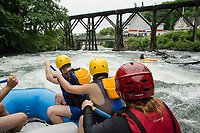 "Joe Astle, Jenisha Shrestha and Alicia Carroll paddle hard as they approach the trestle during Franklin's first whitewater festival ""Winni River Days"" with Mill City Park Saturday afternoon.  (Karen Bobotas/for the Laconia Daily Sun)"