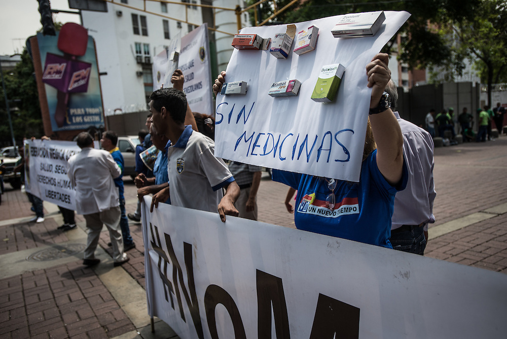 "CARACAS, VENEZUELA - APRIL 13, 2016:  Doctors, patients and their families block traffic during a protest against the hospital crisis.  This woman held a sign with empty boxes of medicines that are widely unavailable because of severe shortages, with ""We don't have medicines"" written in Spanish.  Despite having the largest oil reserves in the world, falling oil prices and wide-spread government corruption have pushed Venezuela into an economic crisis, with the highest inflation in the world and chronic shortages of food and medical supplies.  PHOTO: Meridith Kohut for The New York Times"