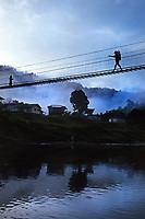 Young boy crossing rope bridge on way to school, Borneo, Malaysia, SE Asia