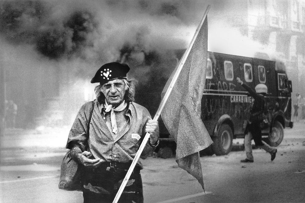 Genova, venerdì 20 luglio 2001. Giornata delle piazze tematiche. Corteo della disobbedienza civile. Pacifista anglosassone nel mezzo degli scontri. .Dopo l'assalto illegale al corteo da parte dei Carabinieri, i manifestanti, forti della pressione di un corteo di circa 10-15.000 persone, si riprendono corso Torino. Una delle camionette resta intrappolata tra i dimostranti. L'autiere viene evaquato e la camionetta è data alle fiamme da alcuni tra i manifestanti.