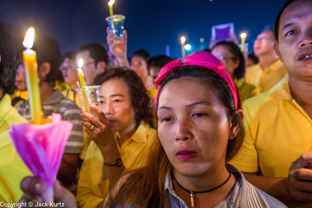 05 DECEMBER 2012 - BANGKOK, THAILAND:  Thais participate in a candle light vigil during the public ceremony to celebrate the birthday of Bhumibol Adulyadej, the King of Thailand, on Sanam Luang, a vast public space in front of the Grand Palace in Bangkok Wednesday night. The King celebrated his 85th birthday Wednesday and hundreds of thousands of Thais attended the day long celebration around the Grand Palace and the Royal Plaza, north of the Palace. The Thai monarch is revered by most Thais as unifying force in Thailand's society, which is not yet recovered from the political violence of 2010.     PHOTO BY JACK KURTZ