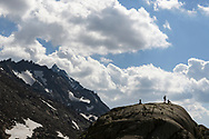 Two female hikers are resting on a glacier polished rock close to the lake Geisspfadsee, Landschaftspark Binntal, Valais, Switzerland
