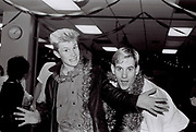 Two teenagers wrapped in tinsel at work Christmas party, London, UK, 1983