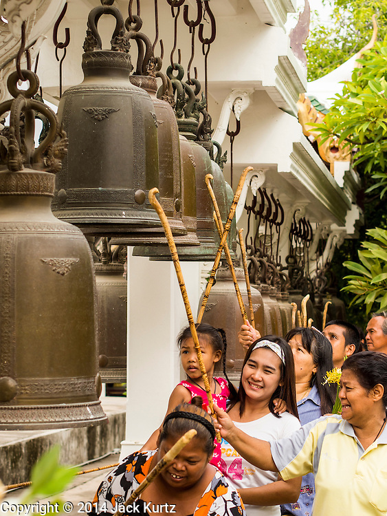 12 JULY 2014 - PHRA PHUTTHABAT, SARABURI, THAILAND: People ring prayers bells before the Tak Bat Dok Mai at Wat Phra Phutthabat in Saraburi province of Thailand. Wat Phra Phutthabat is famous for the way it marks the beginning of Vassa, the three-month annual retreat observed by Theravada monks and nuns. The temple is highly revered in Thailand because it houses a footstep of the Buddha. On the first day of Vassa (or Buddhist Lent) people come to the temple to &quot;make merit&quot; and present the monks there with dancing lady ginger flowers, which only bloom in the weeks leading up Vassa. They also present monks with candles and wash their feet. During Vassa, monks and nuns remain inside monasteries and temple grounds, devoting their time to intensive meditation and study. Laypeople support the monks by bringing food, candles and other offerings to temples. Laypeople also often observe Vassa by giving up something, such as smoking or eating meat. For this reason, westerners sometimes call Vassa &quot;Buddhist Lent.&quot;<br />     PHOTO BY JACK KURTZ