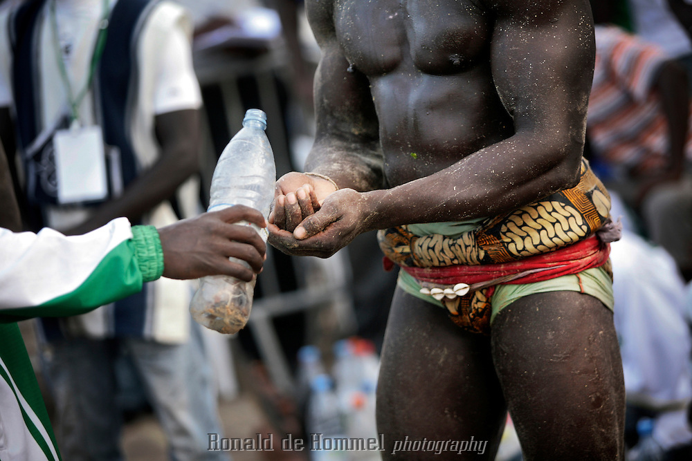 Superstition plays a big role in African traditional wrestling. During the international championship of The Economic Community Of West African States (ECOWAS or CEDEAO) in Dakar Senegalese fighters prepare by covering their bodies in solutions prepared by the Marabout, a medicine man. They also wear small amulets and shells. ..After losing the title to Nigeria last year, the Senegalese home team came out as champion again this time. The championship is prestigious, but commercial wrestling where the fighters are allowed to punch (lutte avec frappe) is more popular with audience and players. The prize money in those fights goes up to 150.000 Euros. The matches attract up to 60.000 spectators. Wrestling has become more popular than football in Senegal in recent years.