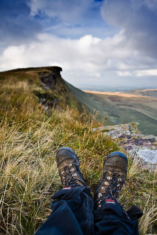 Walkers boots abd view on the Fan Hir escarpment, Brecon Beacons National Park, Powys, Wales