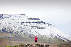 © Licensed to London News Pictures. 25/04/2017. Ingleton UK. A walker stands beneath the snow covered Ingleborough mountain in the Yorkshire Dales today as more snow is expected on higher ground. Photo credit: Andrew McCaren/LNP