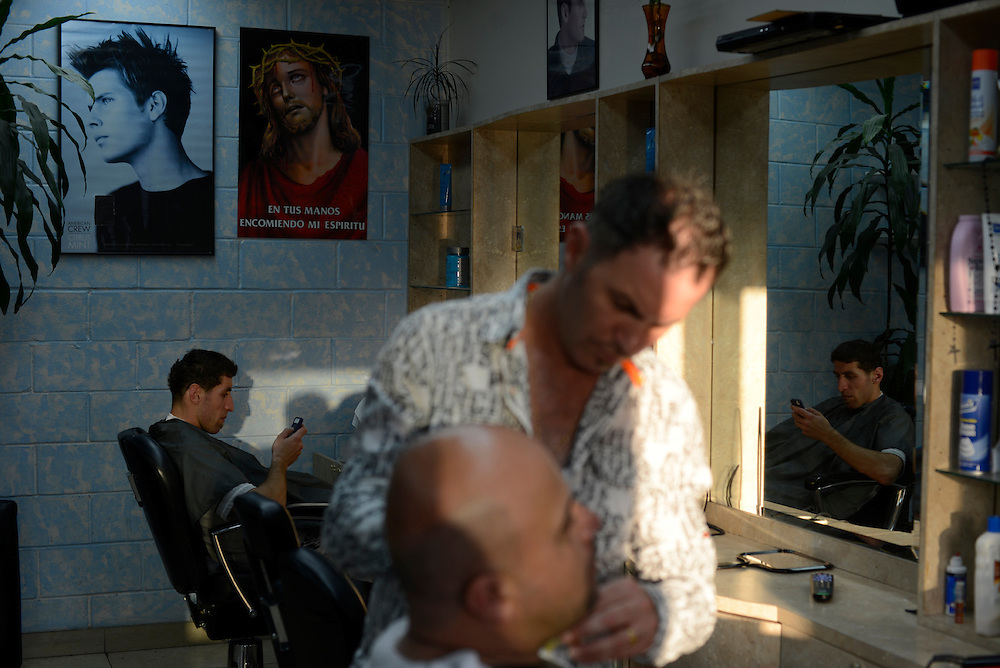 Iraqis refugees getting a haircut and a shave at an Iraqi owned barbershop. Thousands of Iraqi refugees arriving in the town of El Cajon in recent years are transforming the community that lies just north of the US-Mexican border, at the heart of the debate on immigration in the United States, historically dominated by immigrants from Latin America. El Cajon, CA, USA. 04/05/2013.