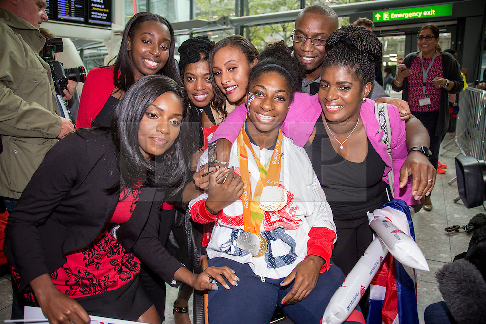 © Licensed to London News Pictures. 20/09/2016. London, UK. Team GB Paralympian KADEENA COX celebrates with family at terminal 5 of London Heathrow Airport after flying on British Airways flight BA2016. Cox carried the GB flag at the closing ceremony after becoming the first Briton in 28 years to win medals in two sports (track cycling and athletics) at the same Paralympics. Team GB finished second in the Paralympics medals table with 147 medals beating their total of 120 at London 2012. Photo credit : Tom Nicholson/LNP