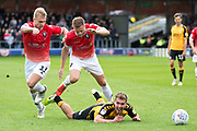Salford City midfielder Sam Hughes and Salford City defender Scott Wiseman foul the opponent during the EFL Sky Bet League 2 match between Salford City and Cambridge United at Moor Lane, Salford, United Kingdom on 12 October 2019.