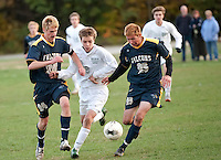 Greg Roemer,  Henry Merrow and Ryan Hill battle for the ball during NHIAA Division  soccer at Hopkinton High School Monday afternoon.  (Karen Bobotas/for the Concord Monitor)