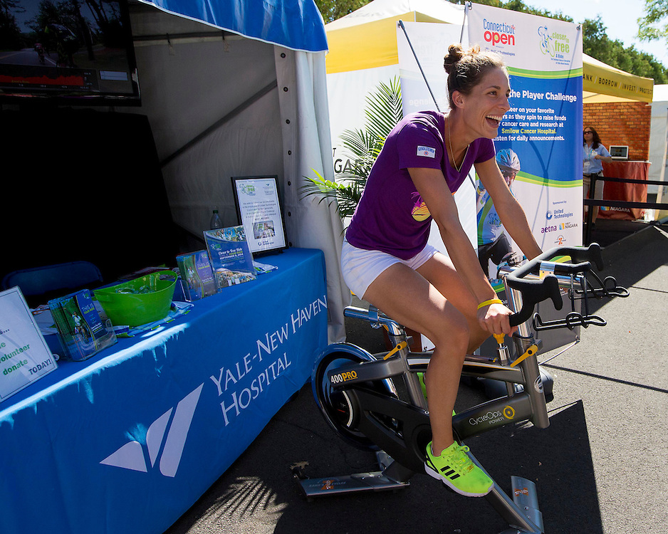 August 19, 2014, New Haven, CT:<br /> Andrea Petkovic bikes on the spin bike to raise money for Yale New Haven Health on day five of the 2014 Connecticut Open at the Yale University Tennis Center in New Haven, Connecticut Tuesday, August 19, 2014.<br /> (Photo by Billie Weiss/Connecticut Open)