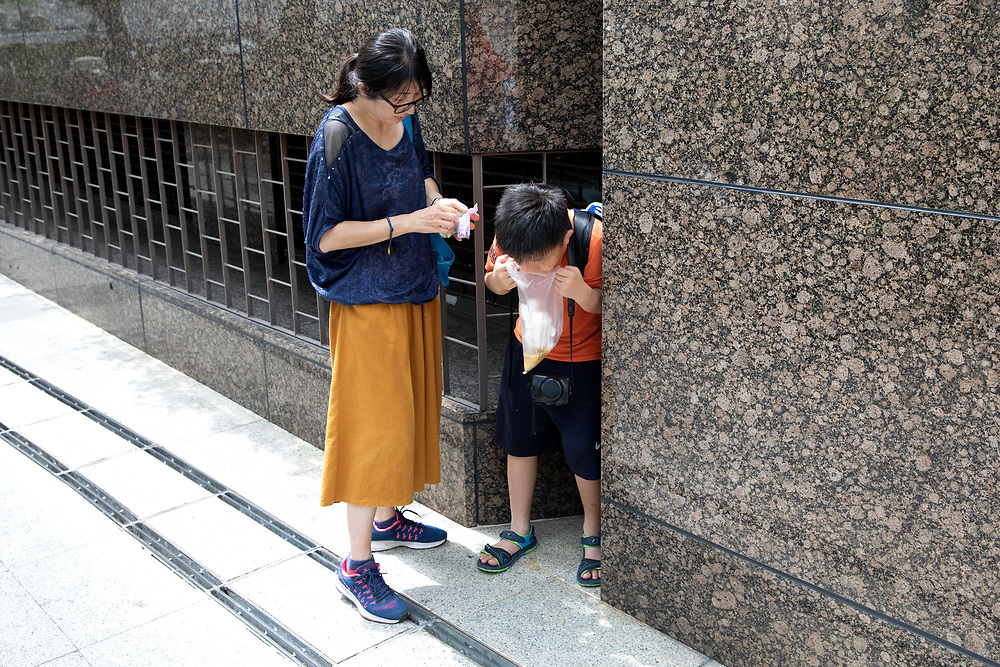 A woman helps as a young boy is sick into a plastic bag at Boat Quay, Singapore.