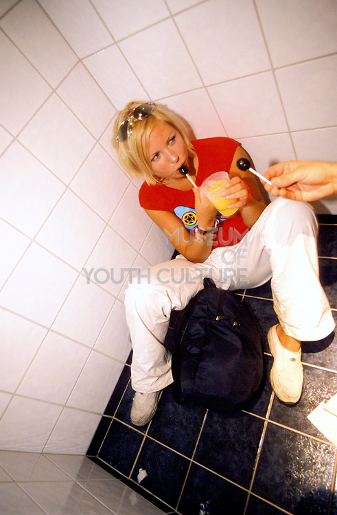 A woman with drink in hand licking a ollypop and sitting on a tiled bathroom floor.