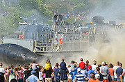 July 6, 2012 - Crowds watch a Navy LCAC (Landing Craft Air Cushioned)  hovercraft land on Hole-in-the-Wall Beach in Niantic, Connecticut during OpSail 2012 opening day celebrations.