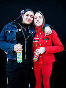 Two teenage girls holding bottles of Fanta soft drink with their arms around each other London 2000