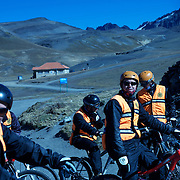 "Mountain Biking on Death Road, Bolivia...A tour group of Mountain Bikers prepare at La Cumbre the starting point of the days ride along death road....The North Yugas Road is a 64 Kilometer road leading from La Paz to Corioico. It is legendary for it's extreme danger and in 1995 the Inter American Development Bank christened is as the ""world's most dangerous road"".. The road was built in the 1930's during the Chaco War by Paraguayan prisoners to connect the Amazon rainforest region of Northern Bolivia to it's capital City La Paz. One estimate is that 200 to 300 travelers were killed yearly along the road. On 24 July 1983, a bus veered off the Yungas Road and into a canyon, killing more than 100 passengers in what is said to be Bolivia's worst road accident..A new stretch of the La Paz-Coroico highroad was opened in 2006 to bypass the notorious stretch known as death road..The danger of the road has now made it a popular tourist destination starting in the 1990's and drawing thrill-seekers and mountain bike enthusiasts who ride on the 64km mainly downhill stretch from La Cumbre, a 4,700 meter peak to Yolosa, a decent of 3600 meter's (11,800 feet). The journey includes breathtaking views of snow covered peaks and towering cliffs and starts along modern asphalted road before entering the jungle itself and the most dangerous and notorious part of the ride. The infamous narrow dirt road, most of the road no wider than 3.2 meter's, is cut into the side of the mountain with sheer drops to the left of up to 600 meter's with virtually no safety rails on the winding steep decent..There are now many tour operators catering to this activity, providing information, guides, transport and equipment. Nevertheless, the Yungas Road remains dangerous. At least 13 of these cyclists died on the ride since 1998, the latest A 28-year-old Israeli traveler was killed in April 2010  the group of cyclists arrived at a heavily foggy area. The woman got separated from the group, and fell into a"