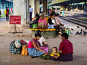 25 NOVEMBER 2017 - YANGON, MYANMAR: Families wait for the Circular Train in the Yangon Central Railroad Station. The Yangon Circular Train is a 45.9-kilometre (28.5 mi) 39-station two track loop system connects satellite towns and suburban areas to downtown. The train was built during the British colonial period, the second track was built in 1954. Trains currently run both directions (clockwise and counter-clockwise) around the city. The trains are the least expensive way to get across Yangon and they are very popular with Yangon's working class. About 100,000 people ride the train every day. A a ticket costs 200 Kyat (about .17¢ US) for the entire 28.5 mile loop.    PHOTO BY JACK KURTZ