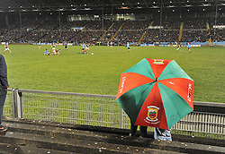 Under Cover of the umbrella Mayo supporters look out on the action at McHale Park on saturday as Mayo took on the Dubs. Pic Conor McKeown