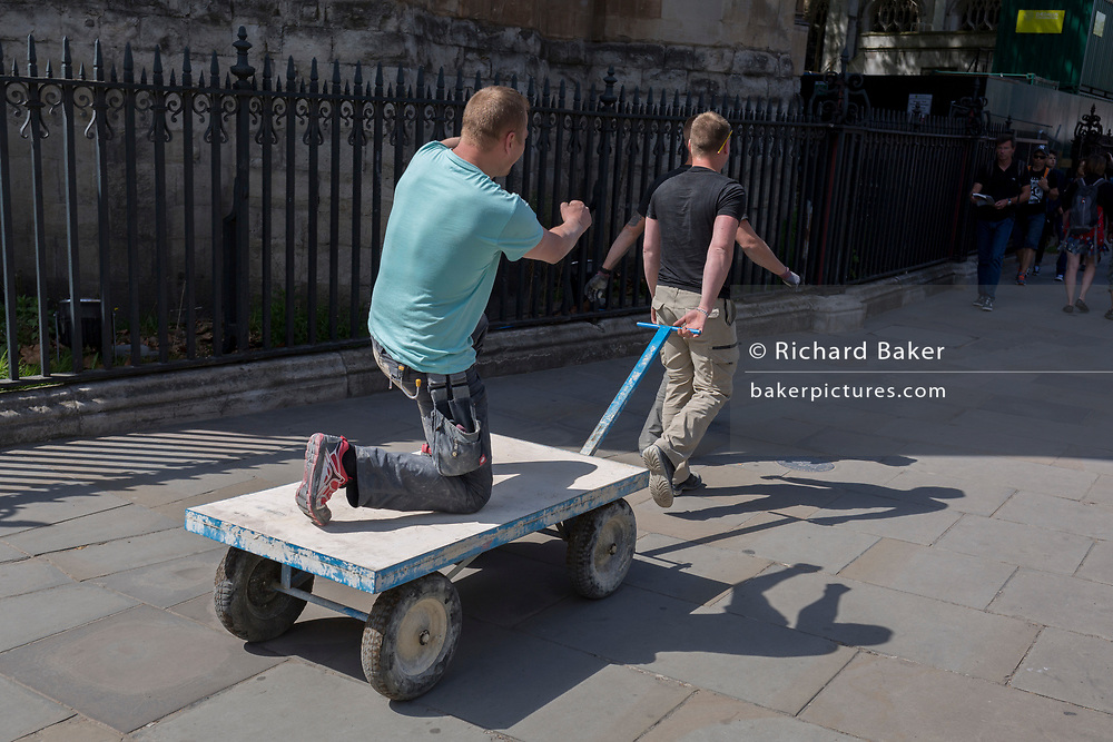 A workmen messes about by reptending to paddle a boat while riding on a trolley cart outside Westminster Abbey, on 9th May 2018, in London, England.